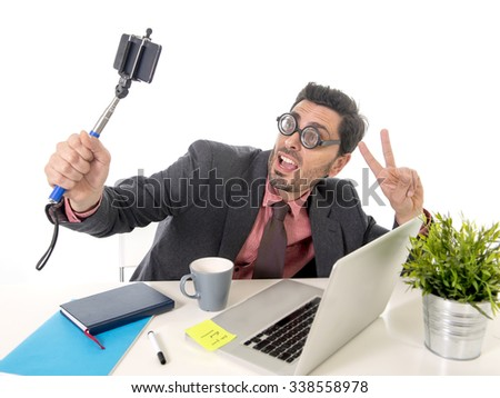 funny nerd businessman with thick glasses in suit and tie working at office desk taking selfie photo with mobile phone camera and stick posing happy and successful isolated on white background