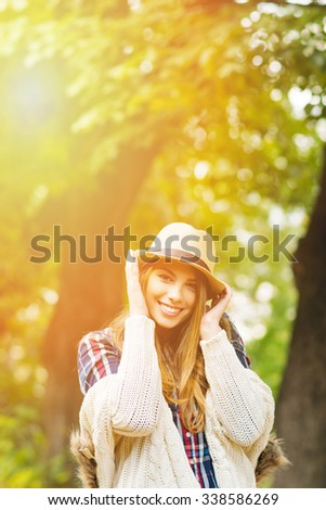 Beautiful young woman in park in autumn. Gorgeous teenage girl in beige hat and sweater outdoors in fall smiling and posing. Vertical, retouched, vibrant colors. #338586269