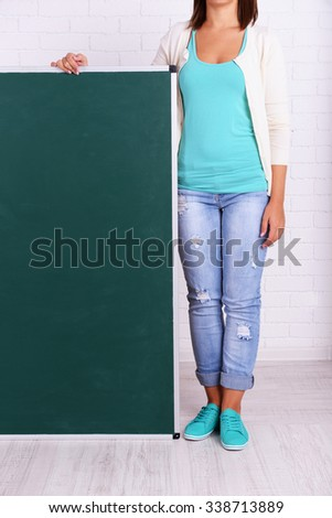 Woman in causal with green blackboard against brick wall, close up #338713889