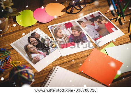 Snow falling against high angle view of office supplies with blank instant photos #338780918