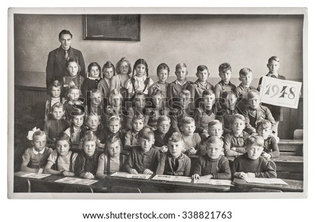 Group of children and teacher in the classroom. Retro picture of classmates in the school. Vintage photo with original film grain, blur and scratches from ca 1948