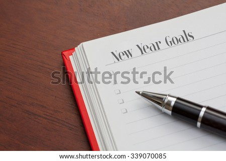 Conceptual,notebook on a wooden table. open diary and pen with new year goals words #339070085