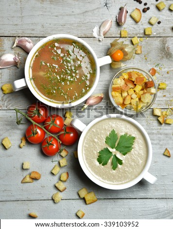 Two soup bowls composition vegetarian mushroom and fish cream soup in bowl with garlic parsley dill and croutons on rustic wood background #339103952