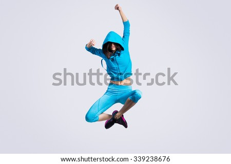 One beautiful young fit modern dancer lady in blue sportswear hoodie sweater working out, dancing and jumping, full length, studio image on gray background #339238676