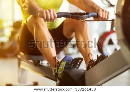 Fit man training on row machine in gym Royalty-Free Stock Photo #339261458