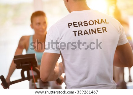 Personal trainer on weights lifting training with  client Royalty-Free Stock Photo #339261467