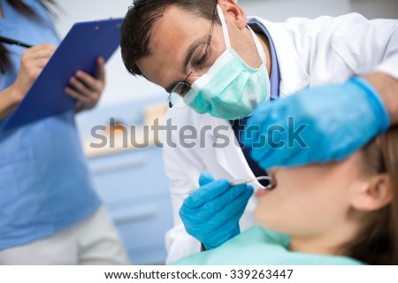 Dentist very  carefully  check up and repair tooth of his young female patient #339263447