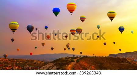 Hot air balloons landing in a mountain #339265343