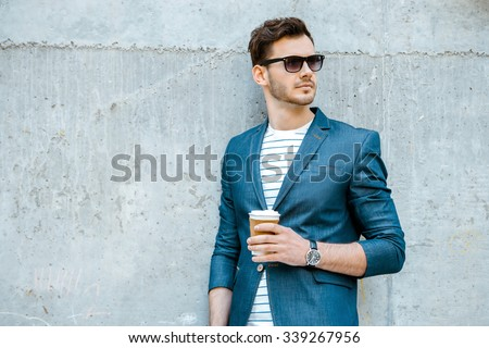Portrait of stylish handsome young man with bristle standing outdoors and leaning on wall. Man wearing jacket, sunglasses, shirt and holding cup of coffee #339267956