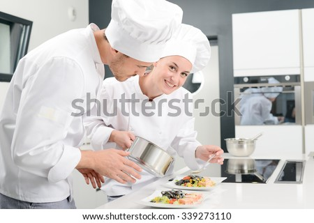 student and teacher in a professional cook school kitchen preparing a plate for restaurant #339273110