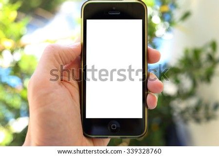 Hand holding smartphone with green leaves background #339328760