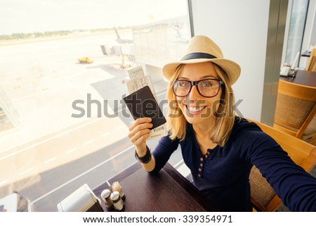 Enjoy traveling! Vacation Selfie. Beautiful young woman in hat taking selfie while waiting for boarding in the airport.