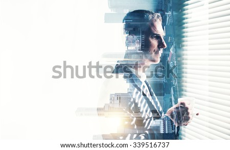 Businessman wearing suit and looking at the window. Double exposure city on sunrise. Horizontal Royalty-Free Stock Photo #339516737