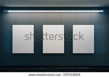Blank picture frames on grey wall with glowing lamp, mock up
