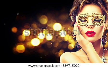 Beauty model woman wearing venetian masquerade carnival mask at party over holiday dark background with magic glow. Christmas and New Year celebration. Glamour lady with perfect make up and hairstyle #339715022