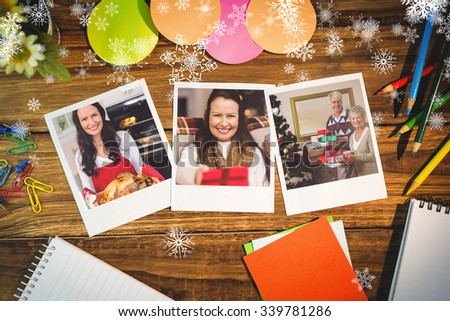 Snowflakes against overhead view of office supplies with blank instant photos #339781286