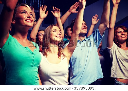 party, holidays, celebration, nightlife and people concept - smiling friends waving hands at concert in club #339893093