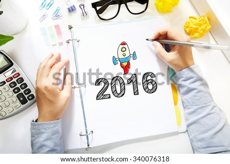 Person drawing 2016 concept on white paper in the office