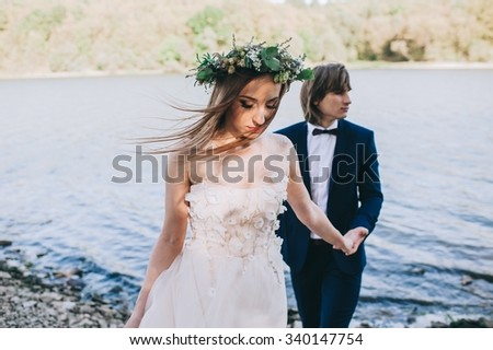 beautiful young couple just married on a walk by the lake #340147754