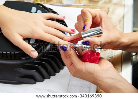 Nails painting with UV dry lamp in blue light woman hands at nail salon #340169390