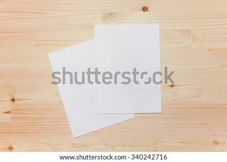Mock up, photo paper on the table, art tools, white sheet, a wooden table. Background light wood #340242716