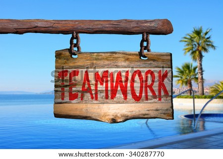Teamwork motivational phrase sign on old wood with blurred background #340287770
