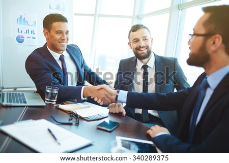 Happy businessmen handshaking after negotiation in office Royalty-Free Stock Photo #340289375