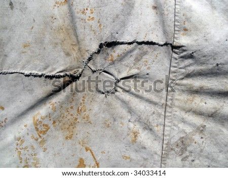 Tattered tarpaulin with traces of rust #34033414