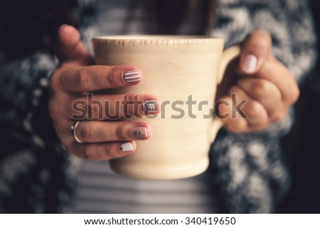Girl's hands holding a cup of coffee. manicure