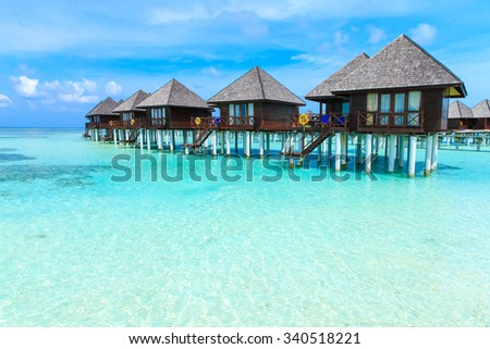 tropical beach in Maldives with few palm trees and blue lagoon #340518221