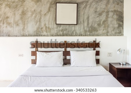 Double bed and furniture with picture frame. The bed room is hotel room.