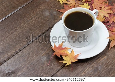 White cup of coffee and color maple leaves are in the upper right corner of photo. #340612367