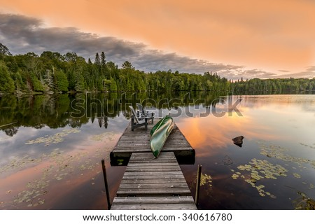 Green Canoe and Chairs on a Dock Next to a Lake at Sunset - Haliburton Highlands, Ontario, Canada #340616780
