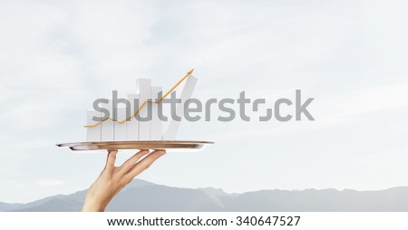 Human hand holding silver plate with growing chart #340647527