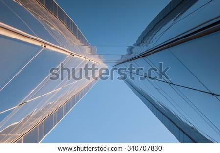 Urban Geometry, looking up to glass building. Modern architecture, glass and steel. . Abstract architectural design. Inspirational, artistic image.Minimal art.  Blue sky background. Minimalist. #340707830