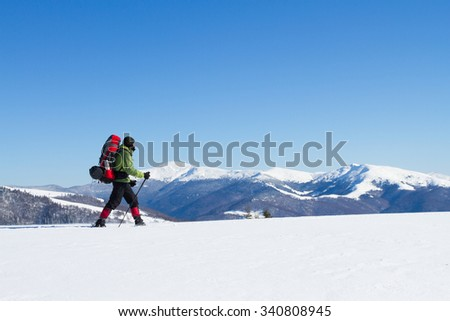 Winter hiking in the mountains on snowshoes with a backpack and tent. #340808945