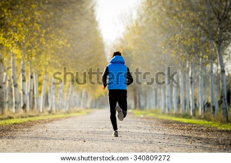 back view young sport man running outdoors in off road trail track with trees in Autumn sunlight wearing jogging vest and sunglasses in fitness, countryside training and healthy lifestyle concept #340809272