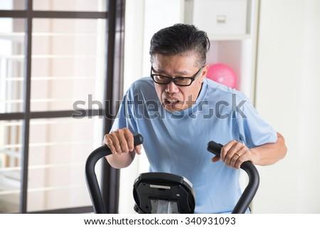 tired asian senior male on exercise bike #340931093