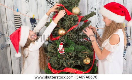 New Year tree decoration concept. Little ladies decorating New Year tree at home: they are hanging multi-coloured balls and red ribbons. #340940690