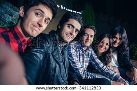 Group of happy young friends smiling while taking a selfie photo in a outdoors party. Friendship and celebrations concept.