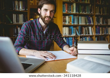 Hipster student studying in library at the university #341118428