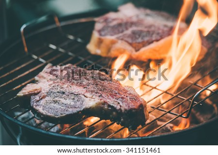 Two t-bone florentine beef steaks on the grill with flames. Toned picture