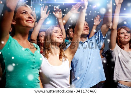 party, holidays, celebration, nightlife and people concept - smiling friends waving hands at concert in club and snow effect #341176460