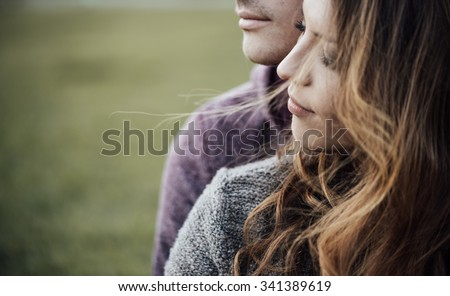 Young loving couple outdoors sitting on grass, hugging and looking away, future and relationships concept Royalty-Free Stock Photo #341389619