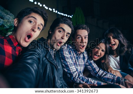 Group of funny young friends shouting while taking a selfie photo in a outdoors party. Friendship and celebrations concept.