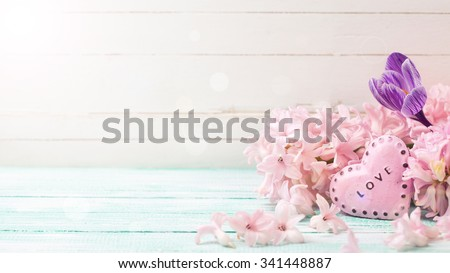 Flowers hyacinths, crocus  and decorative heart  in ray of light on turquoise painted wooden planks. Selective focus. Place for text.