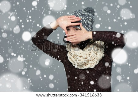 Pretty young woman in winter clothing making a frame with her hands, over snow background #341516633