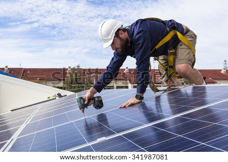 Solar panel technician with drill installing solar panels on roof Royalty-Free Stock Photo #341987081