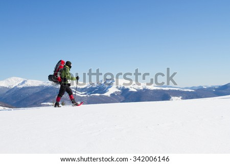 Winter hiking in the mountains on snowshoes with a backpack and tent. #342006146