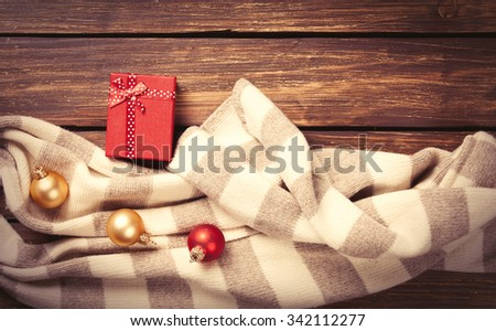 Christmas gifts and scarf on wooden background #342112277